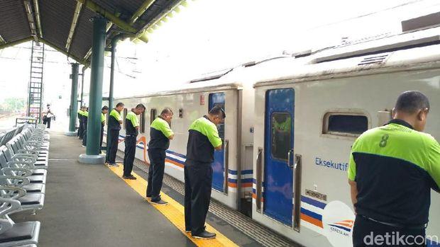 Pegawai PT KAI menunduk saat kereta berangkat /