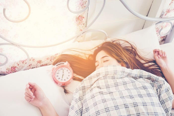 Close up Woman sleeping on bed in Morning with  Alarm clock