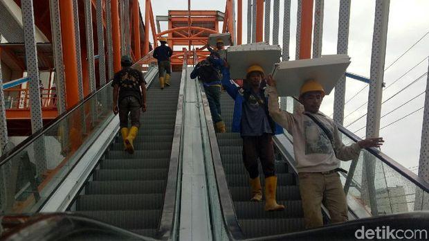 Petugas membersihkan plafon stasiun LRT Palembang yang ambrol