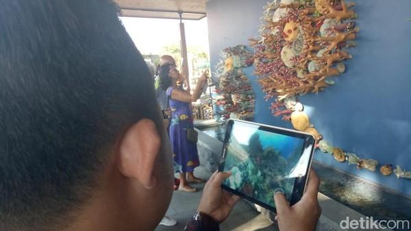 Foto: Ada pula fitur augmented dan virtual reality Semesta Terumbu Karang. Lewat ponsel bak bermain Pokemon Go, para pengunjung bisa menjelajah keindahan bawah laut beserta fauna laut di terumbu karang virtual. Belajar alam bawah laut pun jadi lebih menyenangkan. (Aditya Mardiastuti/detikTravel)