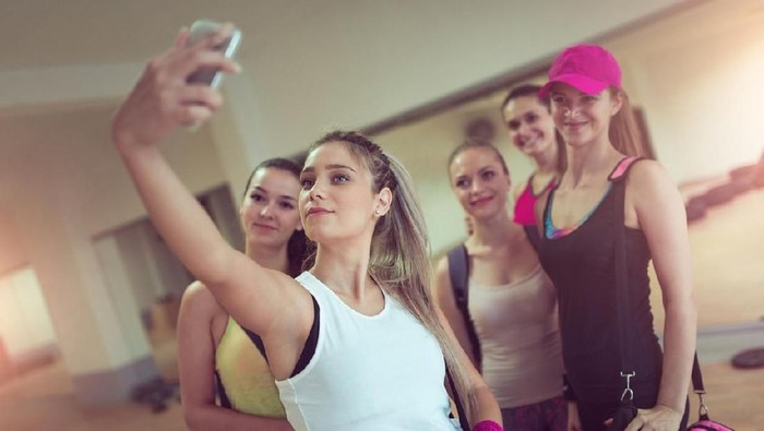 Healthy man prepare for next exercise in gym during hard cross training, while his friends having short rest and take a selfie. They wearing professional sport clothing .