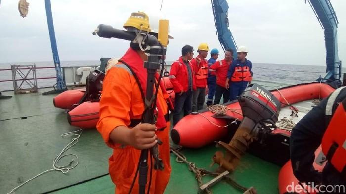 Petugas pencarian membawa ping locator untuk memastikan objek di dasar laut yang ditangkap ditangkap alat sonar. (Matius Alfons/detikcom)