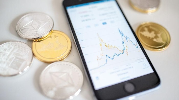 LONDON, ENGLAND - APRIL 25: In this photo illustration of the litecoin, ripple and ethereum cryptocurrency altcoins sit arranged for a photograph beside a smartphone displaying the current price chart for ethereum on April 25, 2018 in London, England. Cryptocurrency markets began to recover this month following a massive crash during the first quarter of 2018, seeing more than $550 billion wiped from the total market capitalisation. (Photo by Jack Taylor/Getty Images)