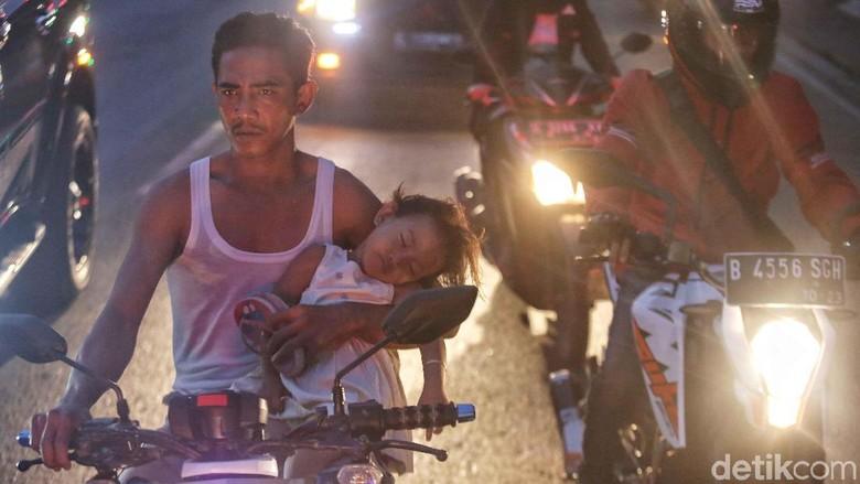 Seorang bapak memegang anaknya yang tertidur saat naik motor Foto: Pradita Utama