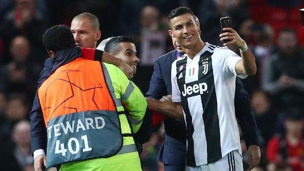 Cristiano Ronaldo menyempatkan diri berfoto dengan fan yang menerobos masuk ke lapangan Old Trafford.