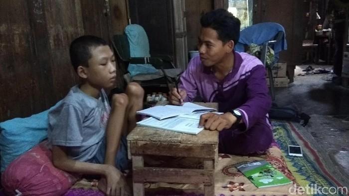 Ilham Irfani saat berlajar ditemani tutornya. Foto: Eko Susanto/detikcom