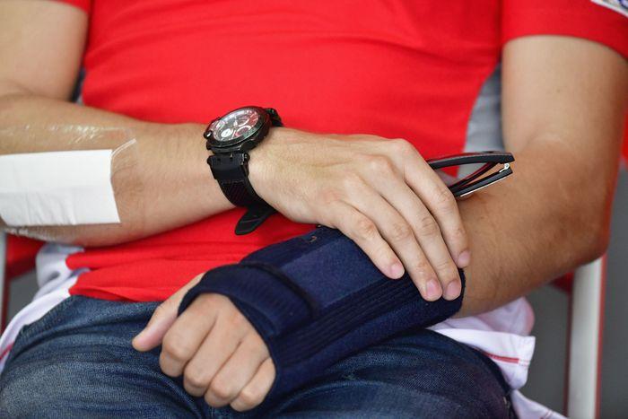 Jorge Lorenzo memegangi tangannya yang masih cedera meski sudah menjalani operasi. Karena belum pulih benar, Lorenzo absen di MotoGP Malaysia (Mirco Lazzari gp/Getty Images)