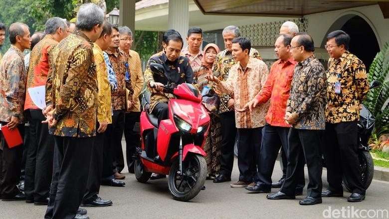 Jokowi duduk di atas motor listrik Gesits. Foto: Andhika Prasetia
