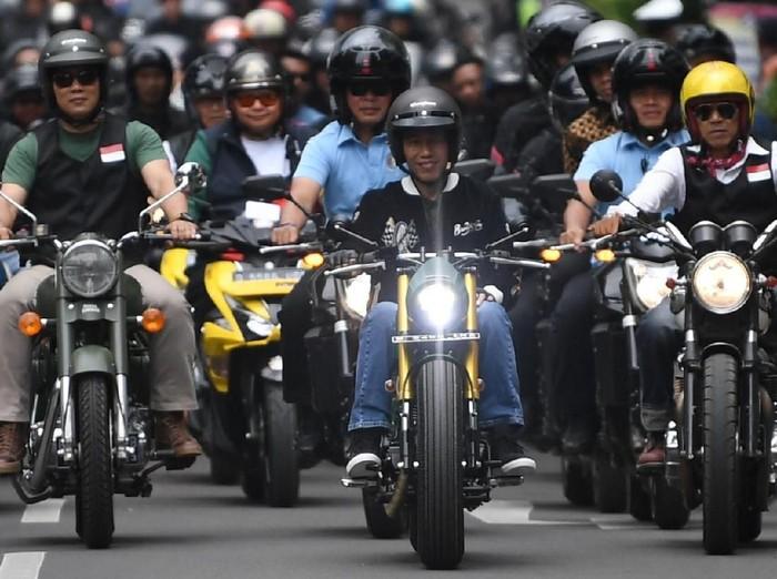 Presiden Joko Widodo (tengah) didampingi Gubernur Jawa Barat Ridwan Kamil (kedua kiri) dan komunitas mengendarai sepeda motor mengelilingi Bandung, Jawa Barat, Minggu (11/11/2018). Kegiatan tersebut merupakan rangkaian Deklarasi Jabar Kondusif yang diikuti 195 komunitas untuk menjaga suasana yang nyaman dan aman guna menjaga persatuan dan kesatuan bangsa. ANTARA FOTO/Wahyu Putro A/nz.