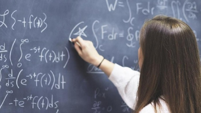 Female STEM student circling an important formula she wrote on the board.