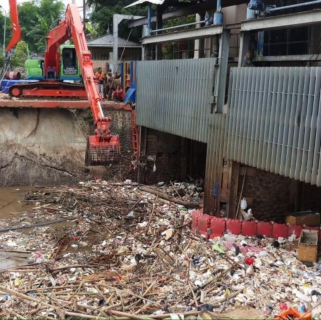 Petugas Bersihkan Sampah yang Menumpuk di Pintu Air Manggarai