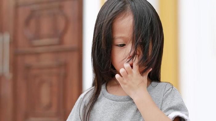 Long hair little child girl pick her nose.