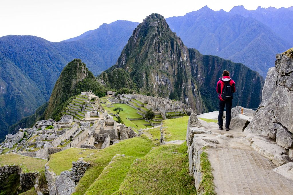Woman standing on a ledge and overlooking the Inca ruins of the city of Machu Picchu seen in the background.