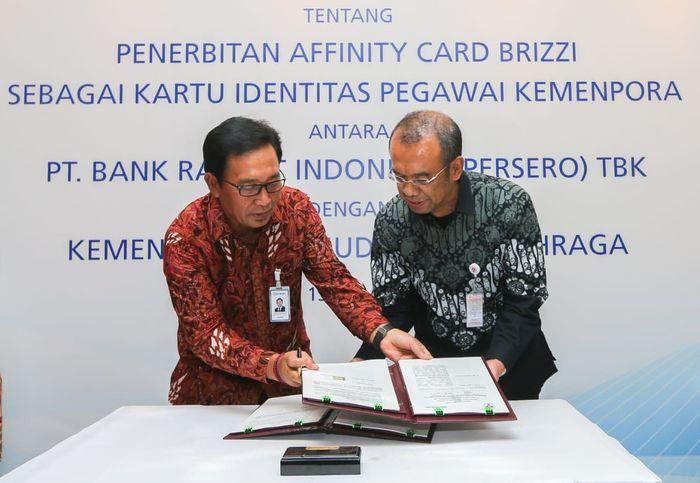 Direktur Hubungan Kelembagaan Bank BRI Sis Apik Wijayanto (kiri) bersama Sekretaris menteri pemuda dan Olahraga RI Gatot S. Dewa Broto (kanan) melakukan penandatanganan Perjanjian Kerjasama tentang penerbitan Affinity Card Brizzi Bank BRI di lingkungan kementerian Pemuda dan Olahraga (Kemenpora) Republik Indonesia, yang dilaksanakan di Gedung Kemenpora RI, Jakarta (13/11). Foto: dok. BRI