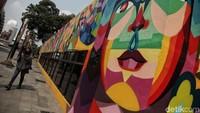 Seorang warga melintas diantara mural di kawasan TIM.