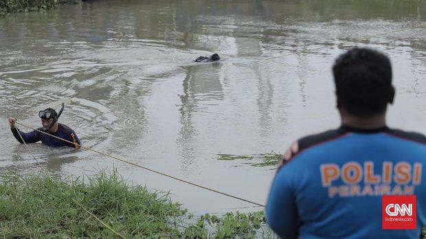 Petugas dari Polda Metro Jaya menerjunkan penyelam untuk mencari linggis yang digunakan tersangka HS untuk menghabisi satu keluarga di Bekasi, di sungai Kalimalang, (17/11).