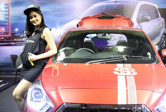 Seorang SPG tersenyum manis di samping mobil modifikasi yang dipamerkan di IMX 2018.