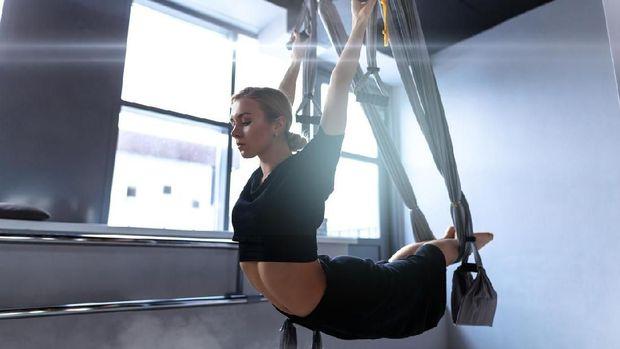Salah satu pose yoga menggunakan hammock.