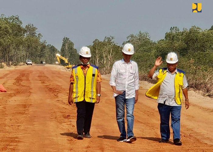 Jokowi berjalan menyusuri jalan yang belum selesai pengerjaannya bersama Menteri PUPR Basuki Hadimuljono. Istimewa/Kementerian PUPR.