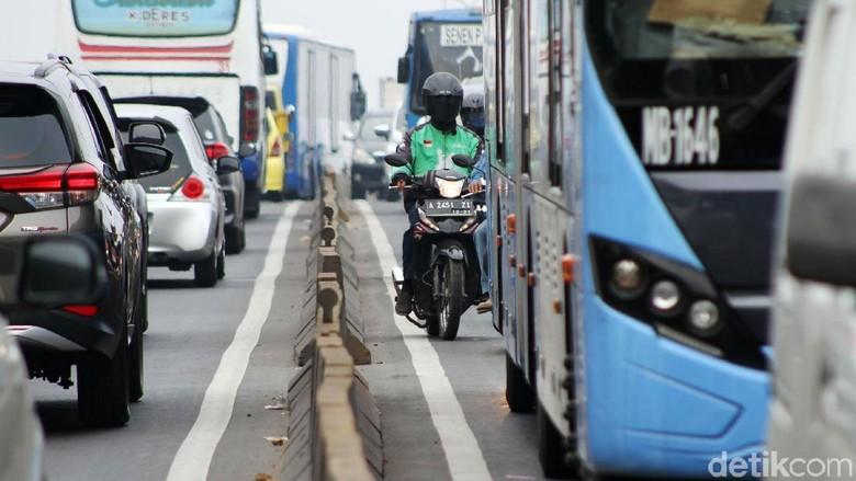 Polisi menilang pengendara sepeda motor yang nekat melintas di Flyover Pesing, Jakarta Barat, Rabu (21/11/2018).