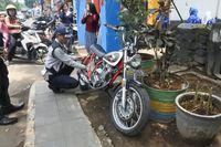 Petugas Dishub Kota Bandung mencabut pentil sepeda motor yang parkir di trotoar.