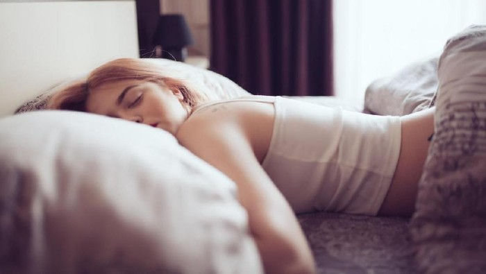 Young woman sleeping in bed. Space for copy.