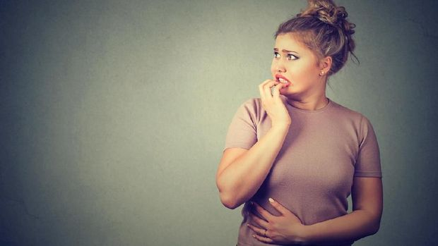 Closeup portrait nervous stressed young concerned woman biting fingernails looking anxiously craving something isolated gray background with copy space. Human emotion face expression feeling reaction