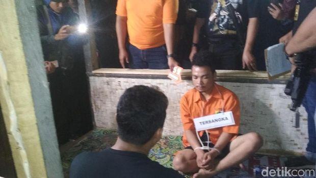 Tersangka pembunuhan satu keluarga di Bekasi, Haris Simamora saat rekonstruksi di Garut, Kamis (22/11/2018)
