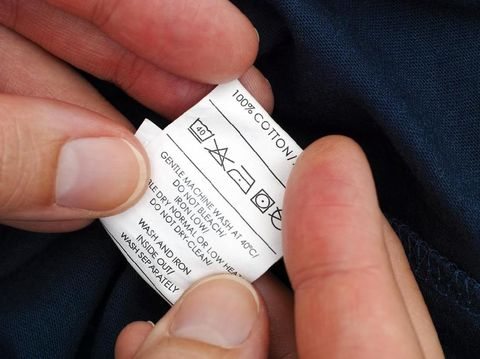 Woman hands holding clothes label with cleaning instructions of dark blue t-shirt.