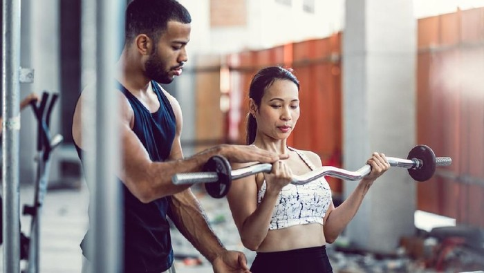 Personal Trainer Coaching a Female Athlete While Lifting Weights