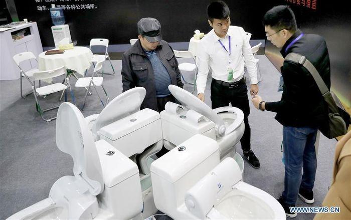 Seorang peserta pameran memperkenalkan tempat duduk toilet pintar dengan penutup sanitasi otomatis. Istimewa/Xinhuanet.