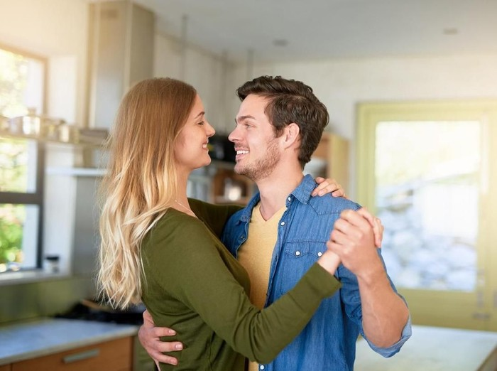 Romantic couple at home. Attractive young woman and handsome man are enjoying spending time together. Sitting on the floor in light modern kitchen.