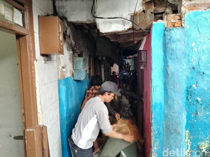 Warga membersihkan area rumahnya yang karena banjir. (Foto: Tri Ispranoto/detikcom)