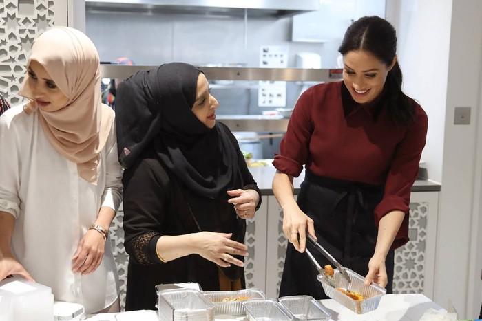 The Duchess of Sussex ini terlihat asyik memasak dan makan bersama dengan para wanita berhijab. Mereka tergabung dalam komunitas Hubb Community Kitchen yang ada di Menara Grenfell, Inggris. Foto: Istimewa/Independent