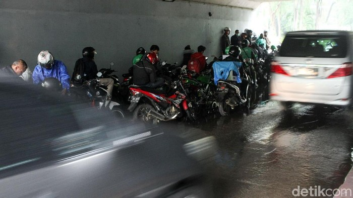 Hujan mengguyur kawasan ibu kota, Senin (26/11/2018). Para pengendara sepeda motor memilih tidak melanjutkan perjalanan dengan berteduh di kolong Semanggi.