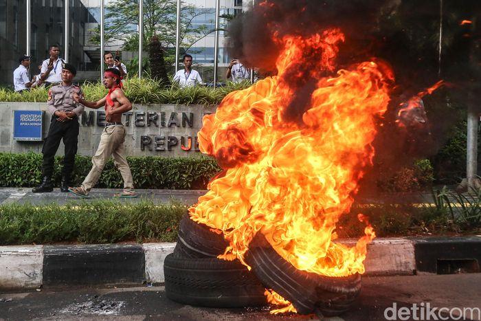 Massa Pergerakan Tani Indonesia Maluku-Maluku Utara (Petani Mal-Malut) membakar ban bekas di depan gedung Kementerian Perdagangan, Jakarta, Senin (26/11/2018).