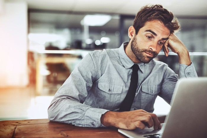 Shot of a handsome young businessman looking bored while working on a laptop in an office
