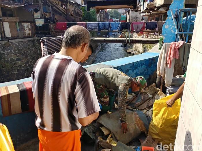 Personel TNI dan warga Astanaanyar bergotong royong membersihkan sampah yang kemarin terbawa arus banjir. (Foto: Tri Ispranoto/detikcom)