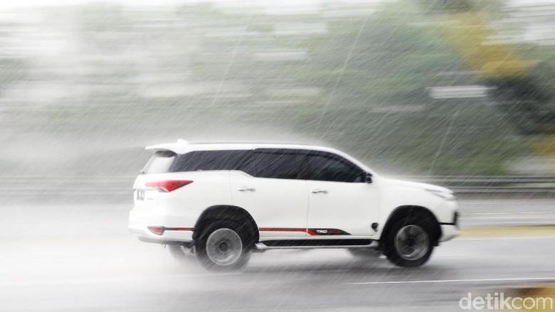 Sebuah mobil melaju saat hujan