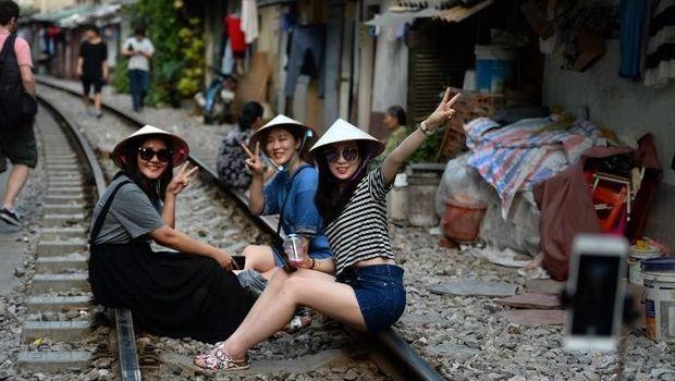 Wisatawan antusias untuk berswafoto di rel kereta di Hanoi.