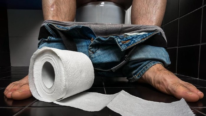 Man suffers from diarrhea is sitting on toilet bowl and toilet paper roll near his legs - diarrhea concept