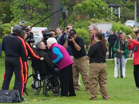 George HW Bush disambut istri, Barbara Bush, setelah terjun payung untuk merayakan ultah ke-90.