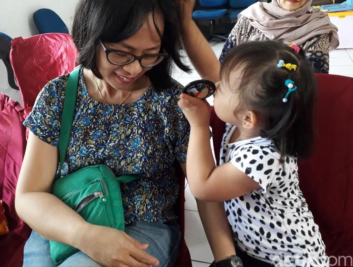 Mama cantik deh abis aku sisirin, begitu mungkin kata Alika (5) kepada ibunya Astrid Unun (42) di sela seminar Octo Touch di Depok, Minggu (2/12/2018). Foto: Rosmha Widiyani/detikHealth