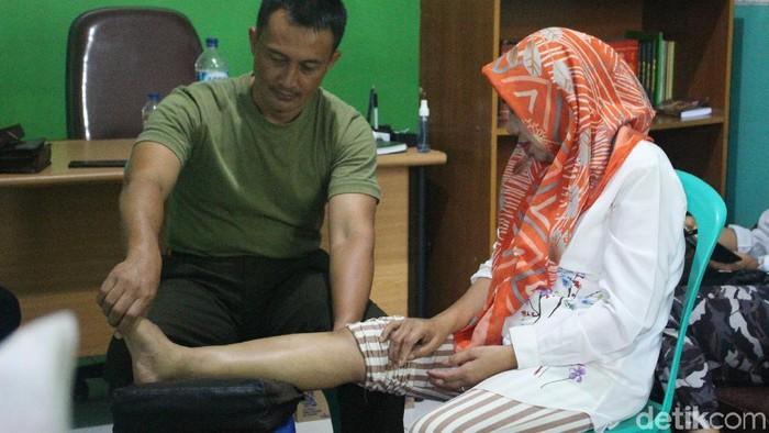 Kapten Tatang mengalirkan listrik ke tubuh pasiennya. (Foto: Kirei/detikHealth)