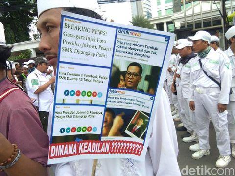 Poster yang dibawa berisi judul berita terkait kasus penghinaan presiden