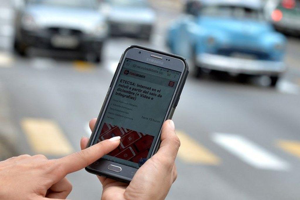Seorang wanita menggunakan ponselnya untuk terhubung ke internet melalui WiFi di Havana, pada 5 Desember 2018. YAMIL LAGE /AFP.