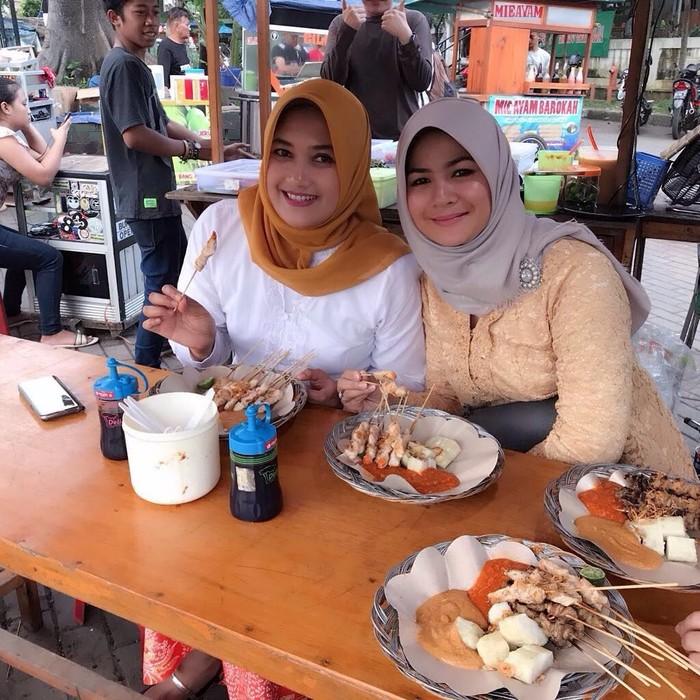Mengenakan jilbab abu-abu, Yane Ardian terlihat menikmati sate taichan di salah satu kedai taichan wilayah Bogor. Foto: Instagram taichanlodaya