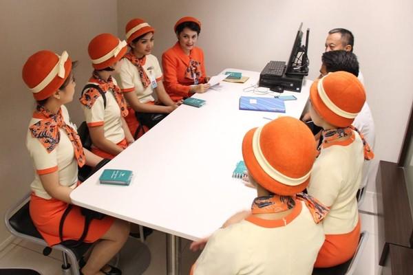 Pramugari mengenakan seragam bernuansa oranye, lengkap dengan topinya (dok Garuda Indonesia)