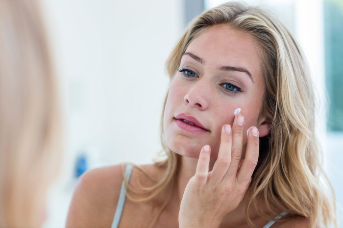 Smiling pretty woman applying cream on her face in bathroom