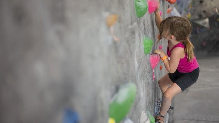 Seorang anak berusia 6 tahun sedang mencoba panjat tebing dalam ruangan. Foto: iStock